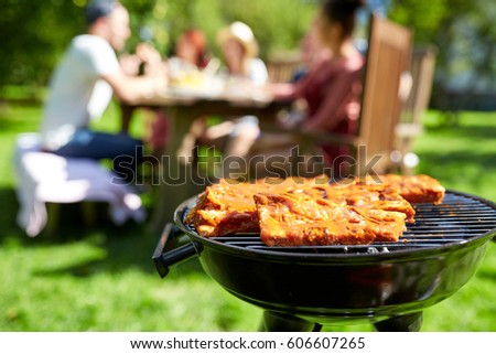 leisure, food, people and holidays concept - meat cooking on barbecue grill at summer party