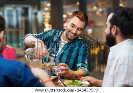 leisure, people and holidays concept - smiling man with friends pouring water from jug at restaurant - stock photo