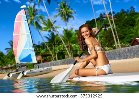 Leisure Sporting Activity. Happy Sexy Fit Woman In Bikini Stand Up Paddling ( SUP, Surfing ) On Surfboard In Sea Near Beach. Recreational Water Sports. Healthy Active Lifestyle. Summer Travel Vacation - stock photo