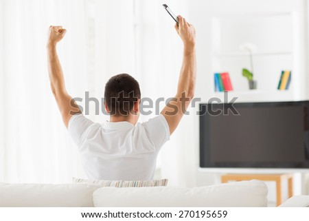 leisure, technology, mass media and people concept - man watching tv and supporting team at home from back - stock photo