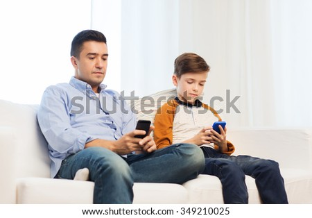 leisure, technology, technology, family and people concept - father and son with smartphones texting message or playing game at home