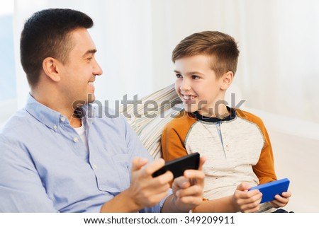 leisure, technology, technology, family and people concept - happy father and son with smartphones talking at home - stock photo