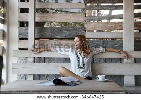 Leisure time. Young woman with coffee or tea cup and magazine on the table  - stock photo