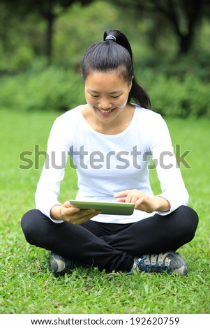 leisure young asian woman use digital tablet sit on grass