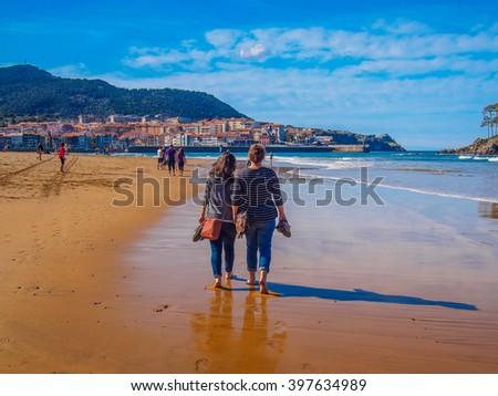 Lekeitio beach island on sunny day couple women - stock photo