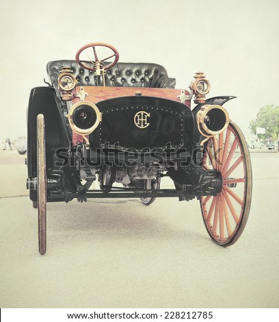 LELYSTAD, THE NETHERLANDS - JUNE 16, 2013: 1912 IHC highwheeler delivery wagon is on display at the annual National Oldtimer day. Textured filtered image in a nostalgic retro look.  - stock photo