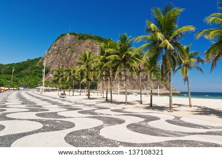 Leme and Copacabana beach with palms and mosaic of sidewalk in Rio de Janeiro - stock photo
