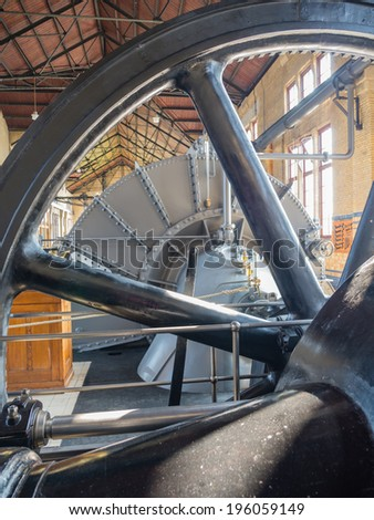 LEMMER, NETHERLANDS - 2 MARCH 2014: Flywheel inside the machine room of the historic Wouda steam pumping station from 1920, the largest of its kind ever built still in operation - stock photo