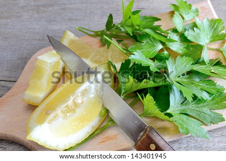 lemon and chopped parsley on wooden cutting board natural