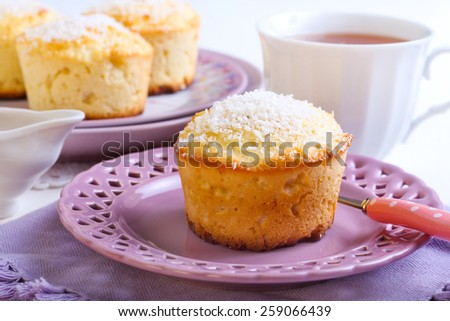 Lemon and coconut cakes on plate and cup of tea - stock photo