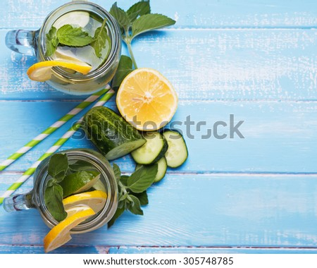 Lemon and cucumber detox water in glass jars on blue colored wooden background, top view - stock photo