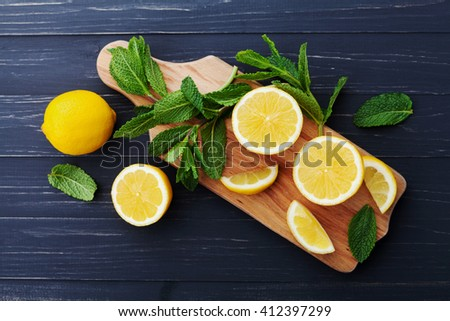 Lemon and mint leaves served on wooden kitchen board on black rustic table, ingredient for summer cocktails and lemonade, top view - stock photo