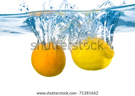Lemon and orange fell into the water. Close-up. Isolated on white. - stock photo
