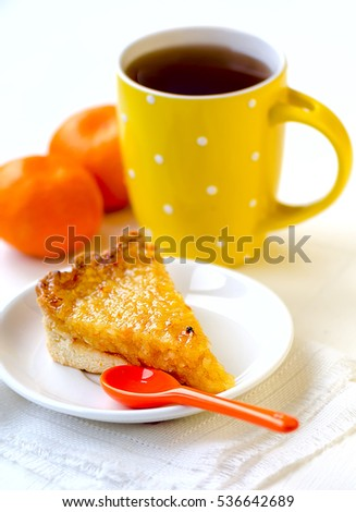 Lemon and orange tart with tea and tangerines on white background