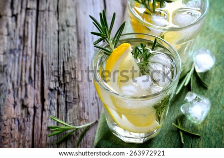 Lemon and rosemary soda with ice cubes in glasses or maybe refreshing summer alcoholic cocktail - stock photo