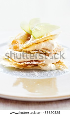 Lemon and vanilla cream cake dessert decorated with apple slices (shallow dof) - stock photo