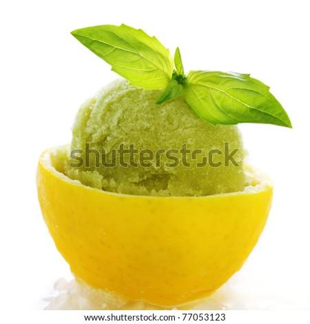lemon- basil sorbet in cups of lemon on white isolated background - stock photo