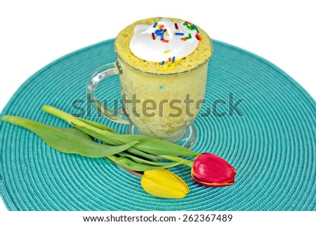 lemon cake in glass mug with yellow and red spring tulips on round aqua placemat - stock photo