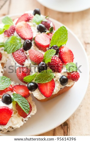 Lemon Cake topped with whipped cream, fresh fruits and mint 1 - stock photo