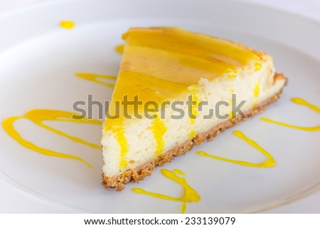 Lemon cheese cake with sauce served on a white plate - stock photo