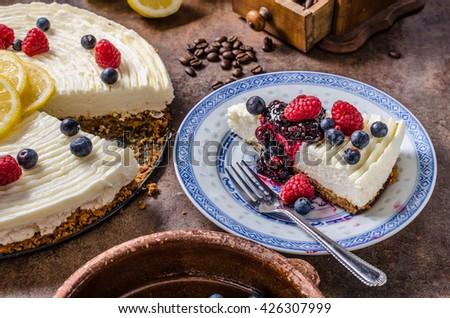Lemon cheesecake with berries, fresh fruits and dark crust - stock photo