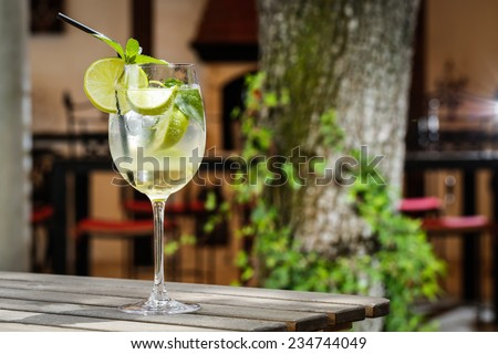 lemon cocktail drink in front of a green tree on a garden table - stock photo