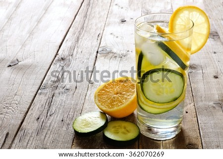 Lemon cucumber detox water in a glass with slices against a rustic wood background - stock photo