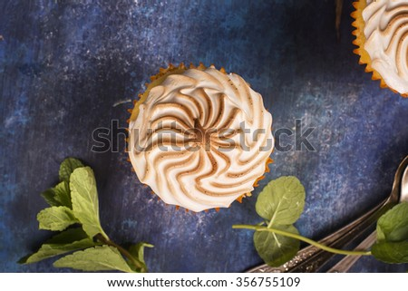Lemon cupcakes with meringue and mint leaves over blue wooden table. Top view. Selective focus - stock photo