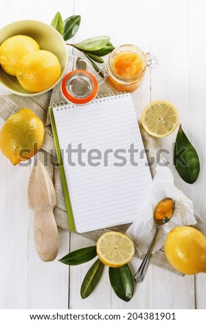 Lemon curd in a glass jar and Recipe Book over white wooden background - stock photo