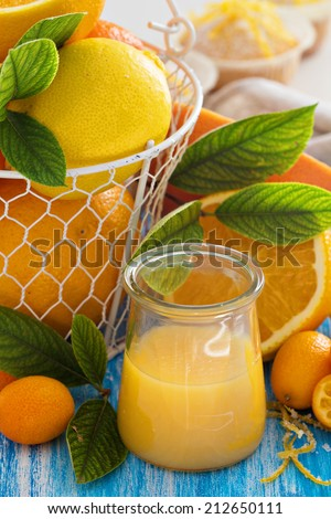 Lemon curd in a small jar with fresh citrus fruits and leaves - stock photo