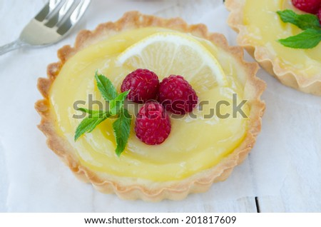 Lemon curd tartlet decorated with raspberry and mint
