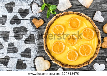 Lemon custard tart, decorated with biscuits in the form of hearts and lemon rings cooked in sugar syrup on an old wooden table, top view - stock photo