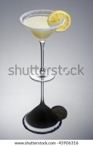 Lemon Drop mixed drink with lemonslice garnish on grey background with reflection - stock photo