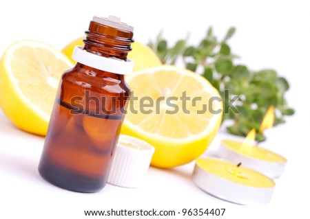 Lemon essential oil, fresh lemon and candles, isolated on white - stock photo