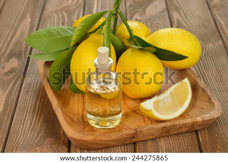 Lemon essential oil on a brown background - stock photo