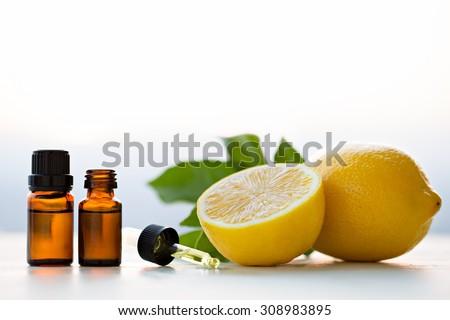 Lemon essential oils in bottles with lemon  - stock photo