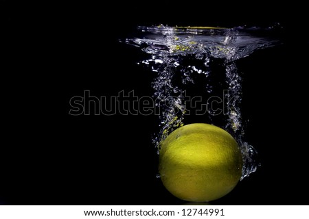 Lemon falling into water - stock photo