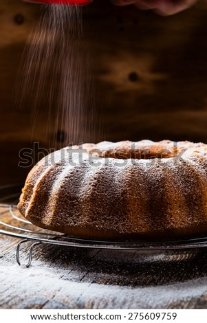 Lemon ginger bundt cake with icing sugar on wooden table, rustic style