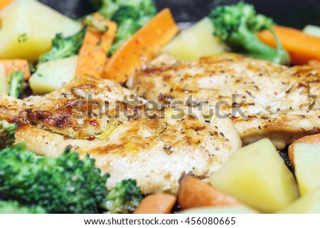 Lemon grilled chicken breast with fried vegetables in pan