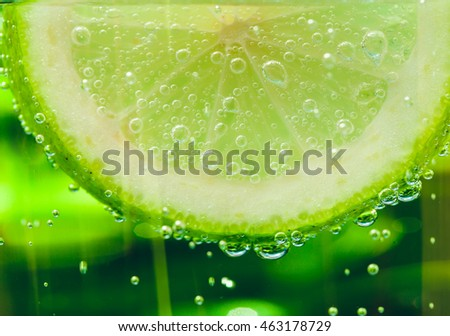 lemon in sparkle water background,sparkle water drops on glass for background or backdrop. Green abstract sparkle water background. Natural green water background. Fresh lemon juice concept.
