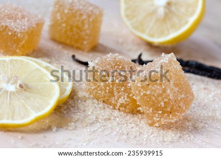 Lemon jujube, marmalade, candied fruit jelly in brown sugar with cinnamon, slices and half of lemon on a wooden table - stock photo