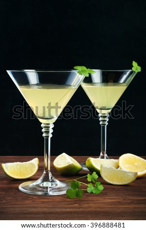 Lemon liqueur with glass goblets on a wooden board. Near slices of lemon and lime. Black background. Place for writing text or recipe.
