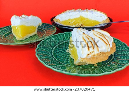 Lemon Meringue Pie being sliced and served on green plates against red background. - stock photo