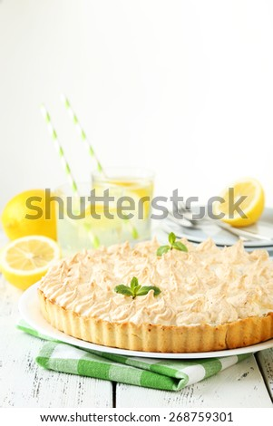 Lemon meringue pie on plate on white wooden background - stock photo