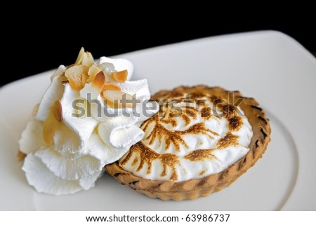 Lemon meringue pie & whipped cream: individual pie with meringue topping served with whipped cream on the side. Shot on black. - stock photo