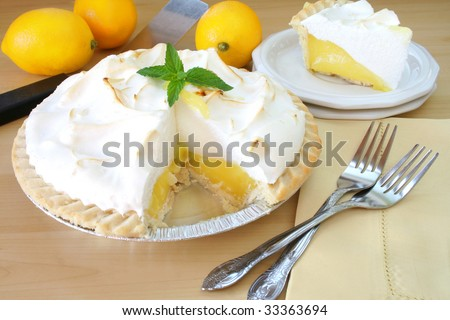 Lemon Meringue pie with a slice cut out and served on a plate, surrounded by fresh lemons and forks. - stock photo