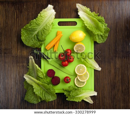 lemon , mini tomatoes carrot and beetroot an lettuce on green plastic cutting surface on wooden background - stock photo