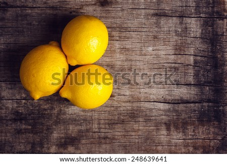 Lemon on old wooden background. Shallow depth of field, toned photo. - stock photo