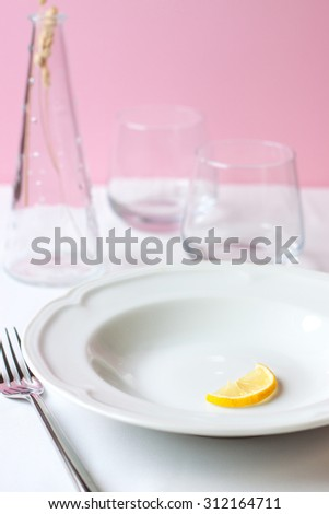 Lemon on white ceramic plate on white table with glass on a pink background