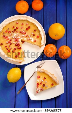 Lemon pie with condensed milk decorated with fresh cranberries and whole oranges and clementines on deep blue table topview - stock photo